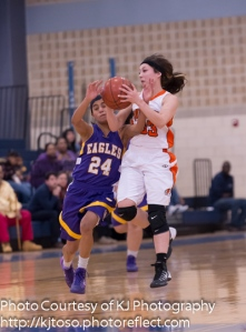 Burbank guard Alejandra Martinez secures a loose ball as Brack's Miranda Acuna charges in to gain possession.