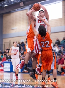 Fox Tech's Ruben Hernandez draws contact from two Burbank players, but scores two points.