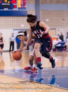 Jefferson's Sasha Barrientos corrals a loose ball as YWLA's Abigail Moreno takes a swipe.