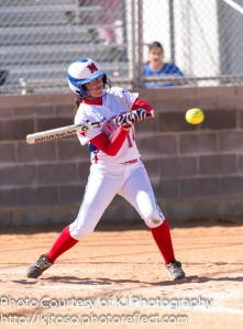 Memorial's Esther Martinez (14) takes a cut at Nikki Velasquez's pitch.