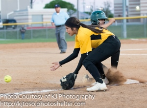 East Central third baseman Alexis Macias receives a throw from the outfield as a Southwest runner slides into the base.