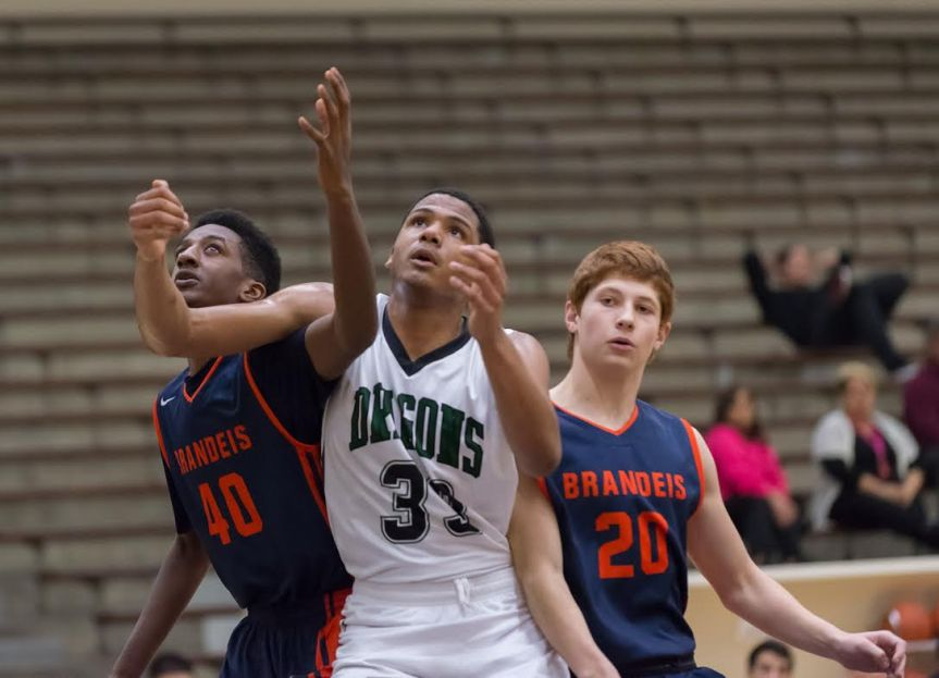 Southwest senior Aaron Embry positions himself for a rebound between Brandeis' William Raeford (40) and Josh Thompson (20) in a first-round match Thursday. The Dragons made a strong showing against the eventual champion, falling 58-51.