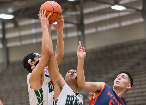 Southwest's Brandon Munoz (32) and Aaron Embry (33) grab a rebound over the Broncos' Ray Gallardo Jr.