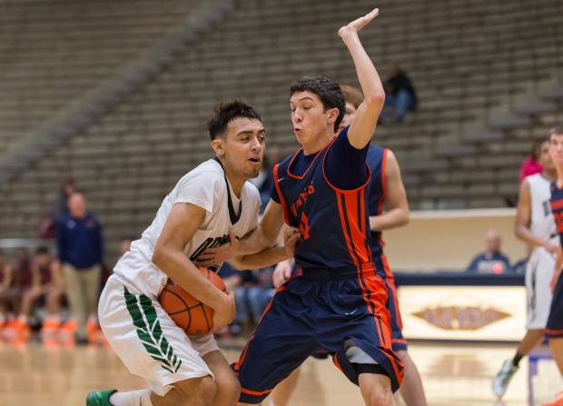 Dragons sophomore Tristan Quintana drives to score two of his 10 points against Brandeis.