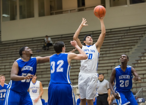 Bobcats junior Andre Flores clears a rebound against MacArthur's front line.