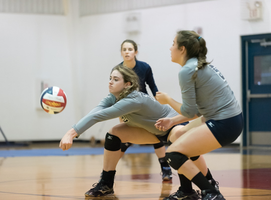 A Providence player executes a dig while a teammate looks on.